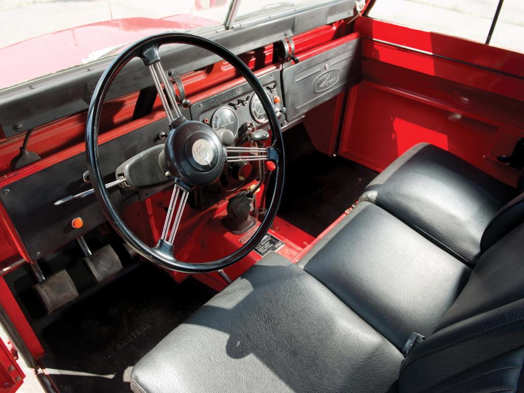 The black steering wheel and black seats look striking inside the red vehicle.